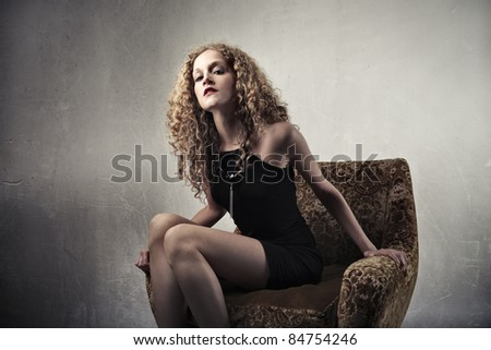 Beautiful woman sitting on an armchair - stock photo