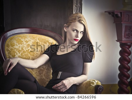 Beautiful woman sitting on an armchair ina luxury interior - stock photo