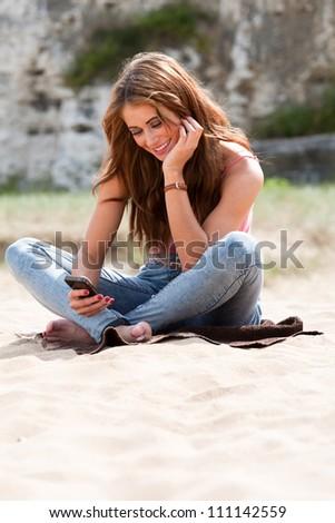 Beautiful woman sitting on beach towel holding phone texting - stock photo