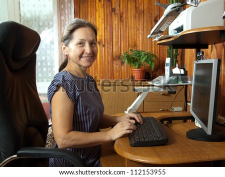 beautiful woman sitting on black chair of the computer - stock photo