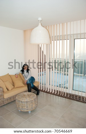 Beautiful woman sitting on couch and relaxing in a modern room with vertical blinds - stock photo