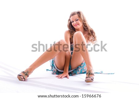 Beautiful woman sitting on floor. Isolated on white background