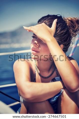 Beautiful woman sitting on the deck of sailboat and cover face from bright sunlight by hand, spending good summer days in the sea - stock photo