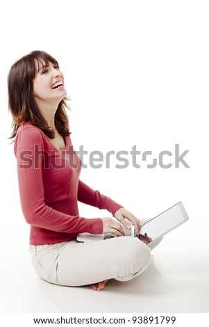 Beautiful woman sitting on the floor laughing  and working with a laptop - stock photo