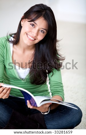 Beautiful woman sitting on the floor studying - stock photo