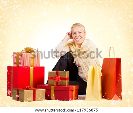 Beautiful woman sitting on the floor surrounded by Christmas presents - stock photo