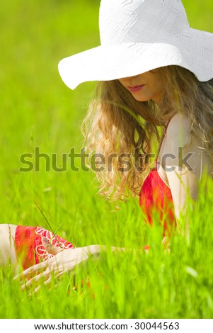 beautiful woman sitting on the grass enjoying summertime - stock photo