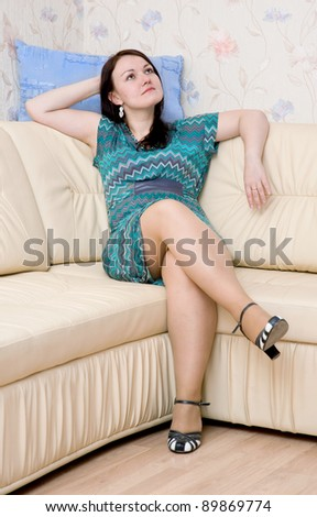 Beautiful woman sitting on the sofa at her home - stock photo