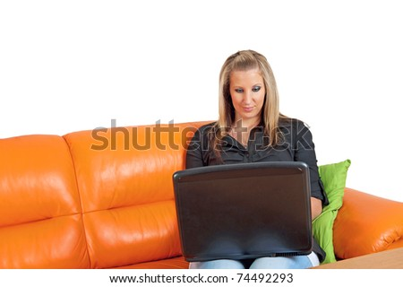 Beautiful woman sitting on the sofa with a laptop - stock photo