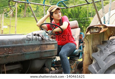Beautiful woman sitting on tractor on the farm