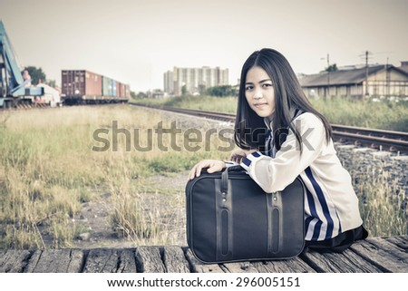 beautiful woman sitting on wood waiting for travel with bag. traveling concept with retro-vintage style.