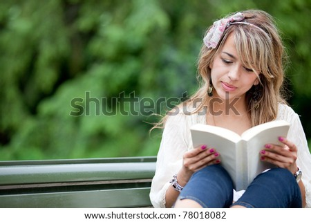 Beautiful woman sitting outdoors in a bench reading a book