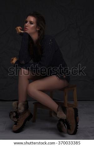 Beautiful woman sitting over dark background - stock photo