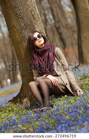 Beautiful woman sitting under the tree enjoys first days of spring - stock photo