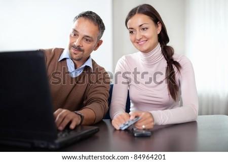 Beautiful woman sitting with a man using laptop - stock photo