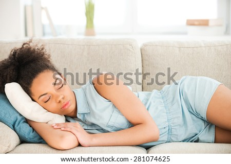 Beautiful woman sleeping. Attractive young African woman sleeping while lying on sofa at home  - stock photo