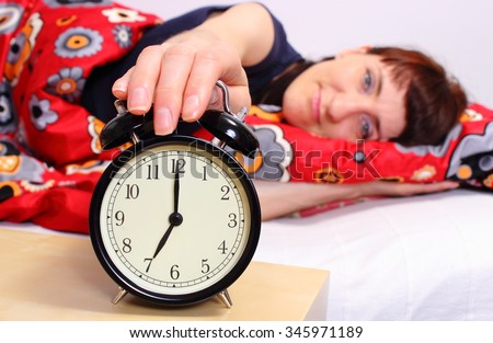 Beautiful woman sleeping on bed in her bedroom and ringing alarm clock set to 7 am - stock photo