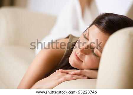 Beautiful woman sleeping on sofa in lounge - stock photo