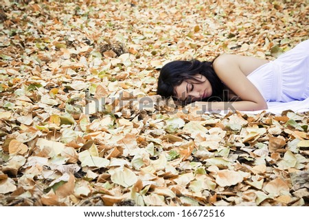 Beautiful woman sleeping over fallen leaves. - stock photo