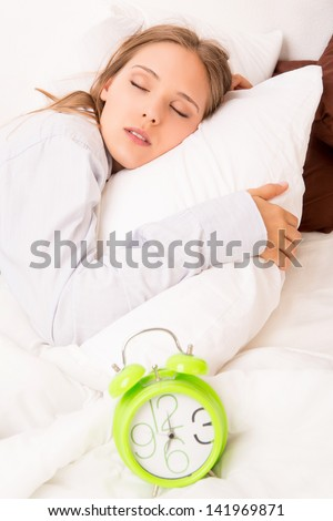 Beautiful woman sleeping with alarm clock on the bed - stock photo