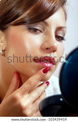 beautiful woman smartens up in front of compact mirror
