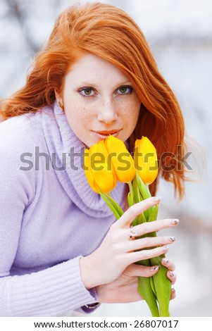 Beautiful woman smelling spring flowers - stock photo