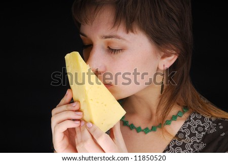 Beautiful woman smells piece of cheese on black background - stock photo