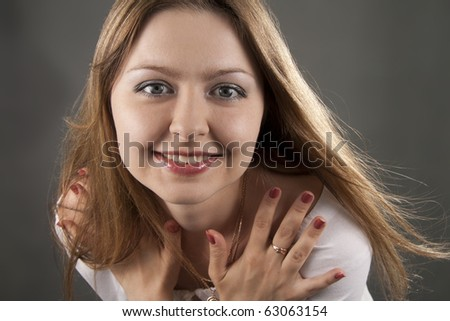 Beautiful woman smiles on a grey background - stock photo