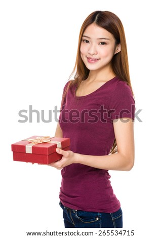 Beautiful woman smiling and holding gift box - stock photo