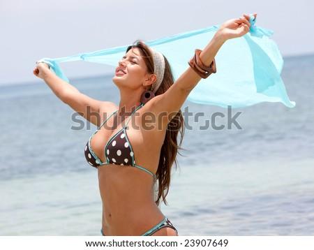 beautiful woman smiling and waving a sarong at the beach - stock photo