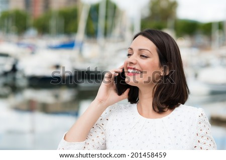 Beautiful woman smiling as she chats on her mobile phone looking away into the distance with a beaming smile of pleasure, marine harbour in the background - stock photo