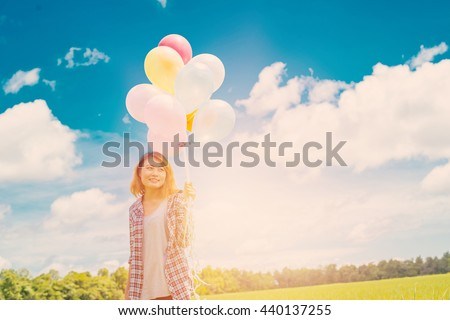 Beautiful woman smiling happiness holding balloons on meadow and blue sky with sunrise, Freedom concept - stock photo