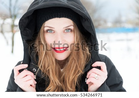 Beautiful woman smiling portrait wearing hood and winter clothes on blue background with copy text space