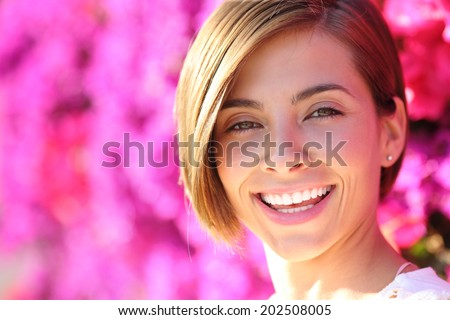 Beautiful woman smiling with white perfect teeth with a warmth lot of pink flowers in the background             - stock photo