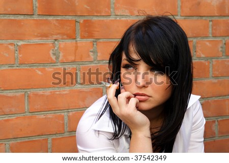 beautiful woman smokes a cigarette - stock photo