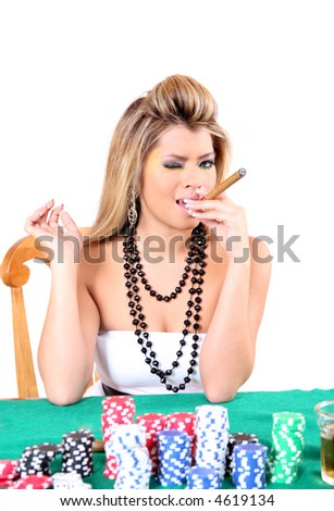 Beautiful woman smoking a cigar while playing poker