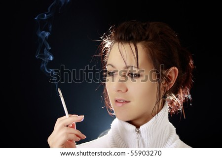 Beautiful woman smoking a cigarette - stock photo