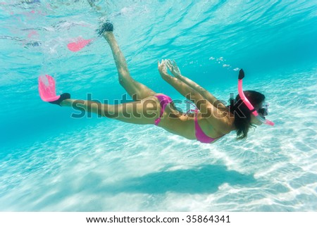 beautiful woman snorkeling in clear tropical turquoise waters - stock photo