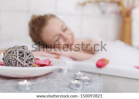 Beautiful woman soaking in a bubble bath with her eyes closed in bliss with focus to the candles in the foreground - stock photo