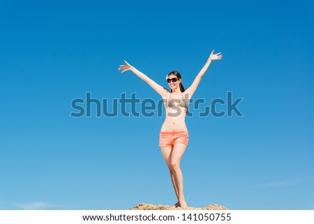 beautiful woman spread her arms against the blue sky, a good time - stock photo