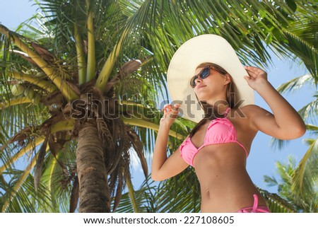 Beautiful woman stand on the palm at the beach - stock photo
