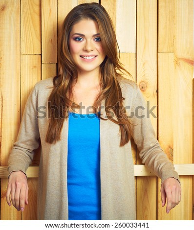 Beautiful woman standing against wooden background. Casual style. Smiling young female model. - stock photo