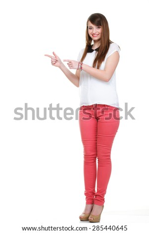 Beautiful woman standing and pointing up. Studio shot. - stock photo