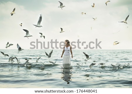 beautiful woman standing at the sea with seaguls around - stock photo