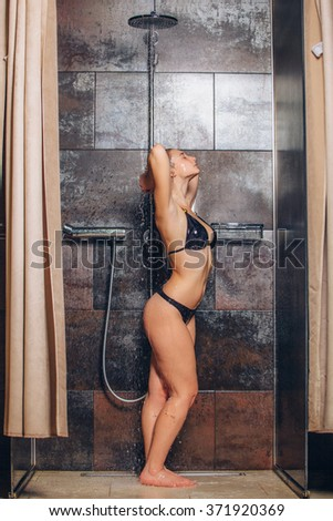 Beautiful woman standing at the shower. In a black bathing suit - stock photo