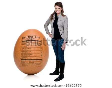 Beautiful woman standing beside Egg Nutrition Facts printed on the outside of a brown egg. - stock photo