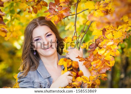Beautiful woman standing in a park in autumn