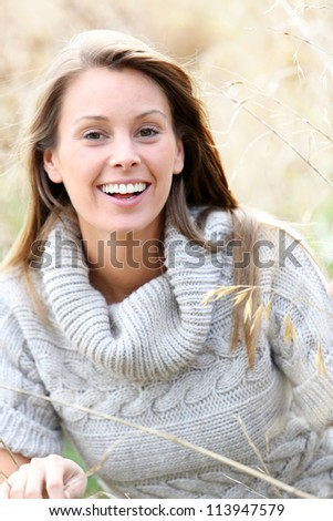 Beautiful woman standing in country field - stock photo