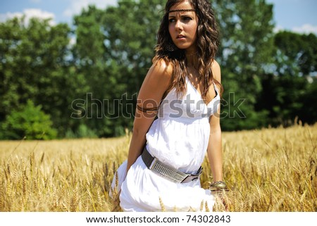 Beautiful woman standing in the middle of a wheat field on a hot summer afternoon. Color image photography with warm tones and a nice fresh feeling of happiness and serenity. - stock photo