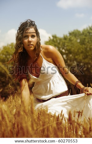 Beautiful woman standing in the middle of a wheat field to feel the hot summer afternoon wind. - stock photo